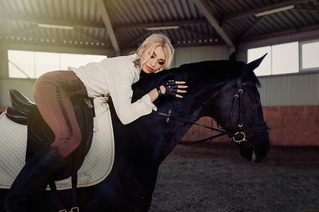 Красивая элегантная молодая белокурая девушка лежит на своей черной лошади, переодеваясь в униформу соревнований, белую блузку и коричневые брюки.