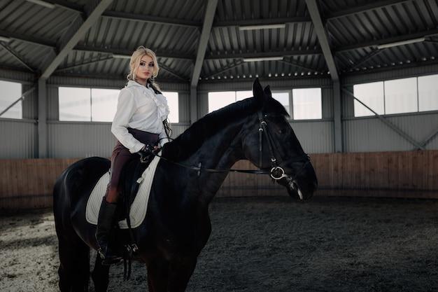 Красивая элегантная молодая белокурая девушка сидит на своей черной лошади, одетая в униформу, в белую блузку и коричневые брюки.
