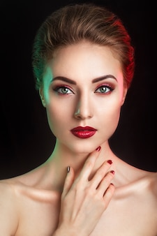 Beautiful elegant young model with red lips and color evening make-up.