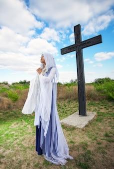 큰 십자가 근처의 아름다운 엘프 소녀 가기도하고 있습니다.