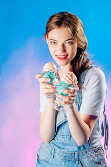 Beautiful emotional girl on a blue background holds in her hands a delicious pink ice cream. sweet sale concept, sale
