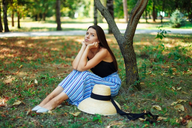 Beautiful emotional girl sitting under a tree in the park, facial expression of resentment and disappointment.
