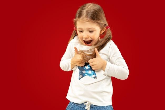 빨간색 배경에 고립 된 아름 다운 감정 어린 소녀입니다. 제스처를 표시 하 고 가리키는 행복 한 아이의 절반 길이 초상화. 표정, 인간의 감정, 어린 시절의 개념.