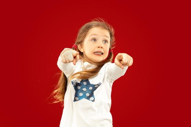 빨간 공간에 고립 된 아름 다운 감정 어린 소녀