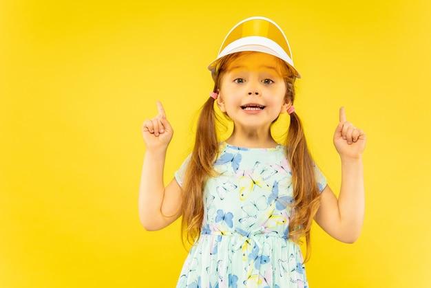 Красивая эмоциональная маленькая девочка, изолированная на желтом
