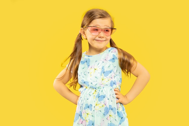 Beautiful emotional little girl isolated. portrait of happy child standing and wearing a dress and red sunglasses. concept of summer, human emotions, childhood.