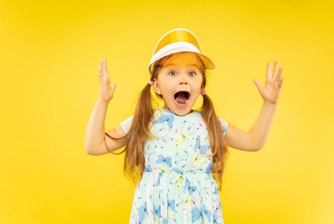 Красивая эмоциональная изолированная маленькая девочка. портрет счастливого и удивленного ребенка в платье и оранжевой кепке. понятие лета, человеческих эмоций, детства.