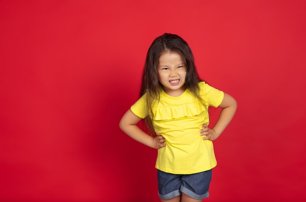 Beautiful emotional little girl isolated on red space. half-lenght portrait of happy child showing a gesture and pointing up. concept of facial expression, human emotions, childhood.