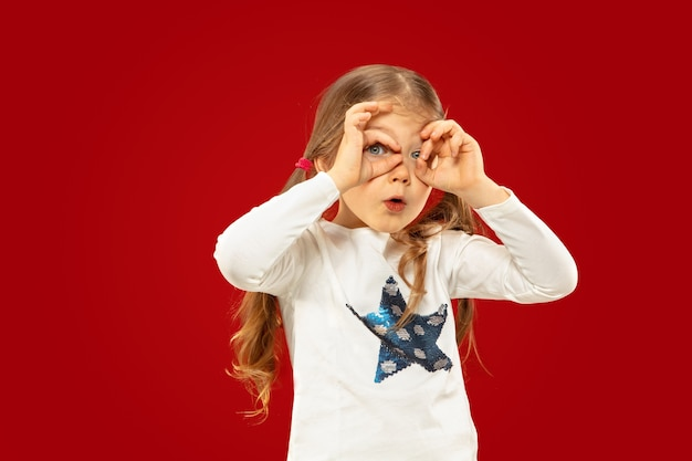 Beautiful emotional little girl isolated on red space. half-lenght portrait of happy child showing a gesture and pointing up