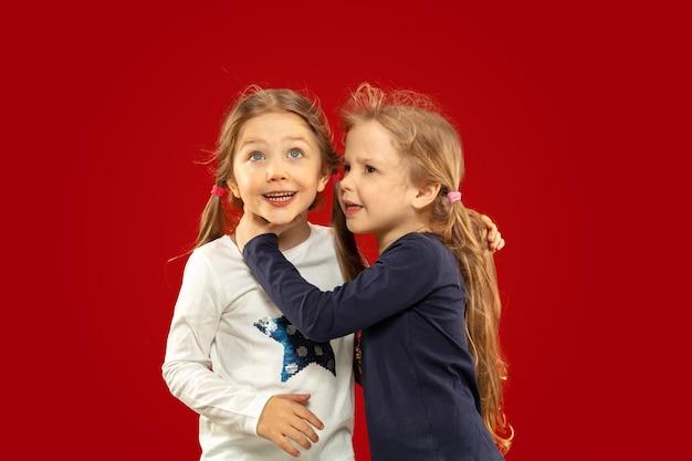 Bella bambina emotiva isolata sullo spazio rosso. ritratto a mezzo busto di sorelle o amici felici in piedi e sorridenti