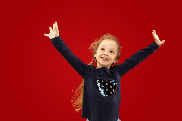 Beautiful emotional little girl isolated on red studio