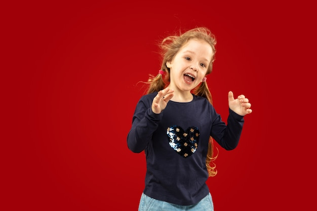 Beautiful emotional little girl isolated on red