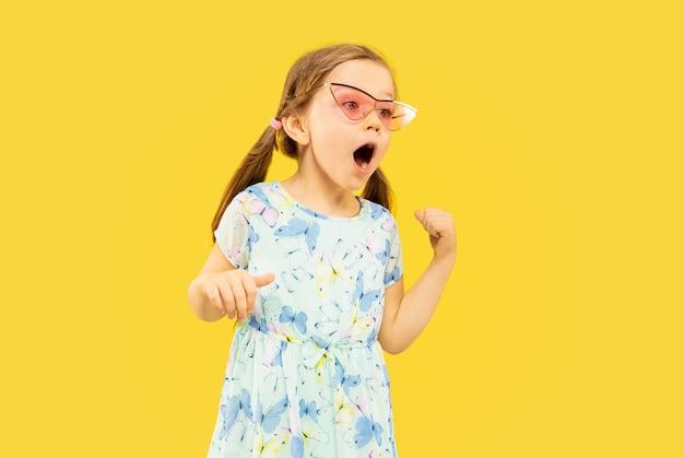 Bella bambina emotiva isolata su spazio giallo. ritratto a mezzo busto di bambino felice in piedi e con indosso un vestito e occhiali da sole rossi