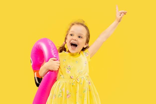 Bella bambina emotiva isolata su spazio giallo