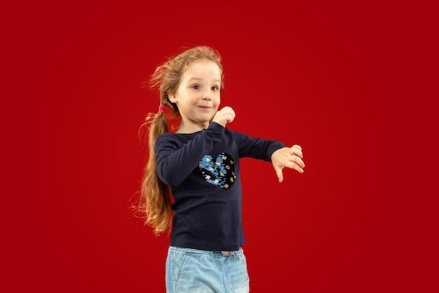 赤いスタジオの美しい感情的な少女