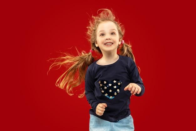 Bella bambina emotiva su studio rosso