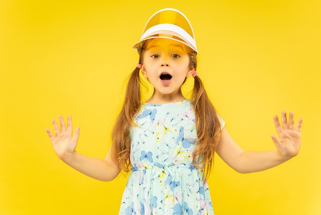 Beautiful emotional little girl on yellow