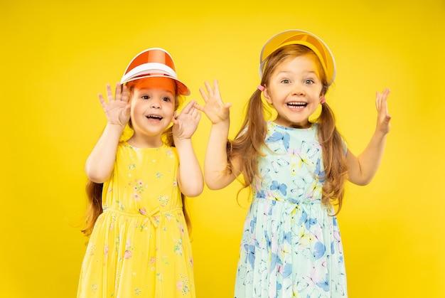 Красивые эмоциональные маленькие девочки, изолированные на желтом