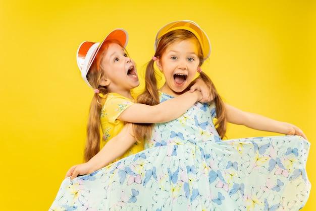 Красивые эмоциональные маленькие девочки на желтом