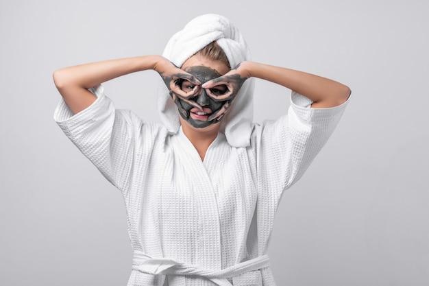 클레이 마스크와 클레이 손으로 그녀의 머리에 수건, 목에 펜던트가 달린 흰색 목욕 가운에서 포즈를 취하는 아름다운 감정 모델. 카메라를 치는 것. 손가락으로 마스크 만들기.