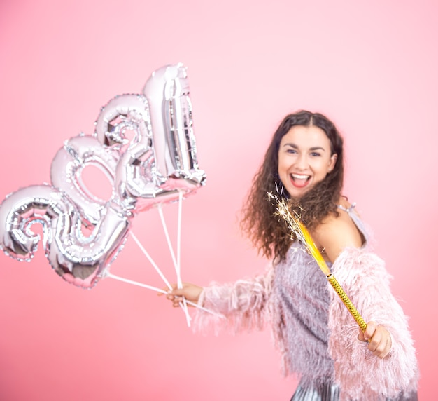 Beautiful emotional young brunette with curly hair festively dressed holding a fireworks candle in her hand and silver balloons for the new year concept