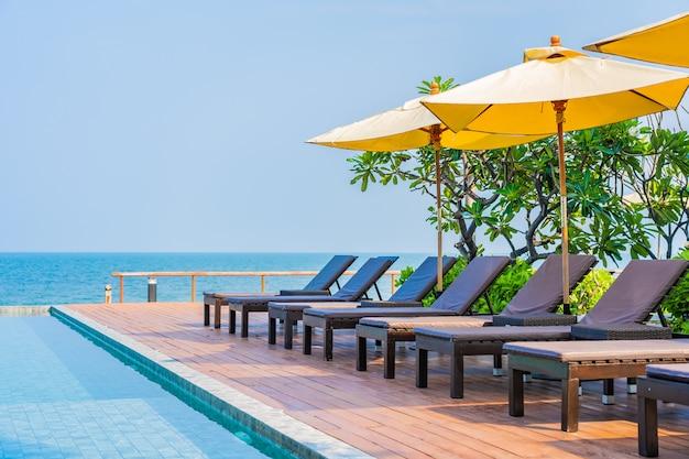 旅行のためのホテルリゾートの屋外スイミングプールの周りの美しい空の椅子傘