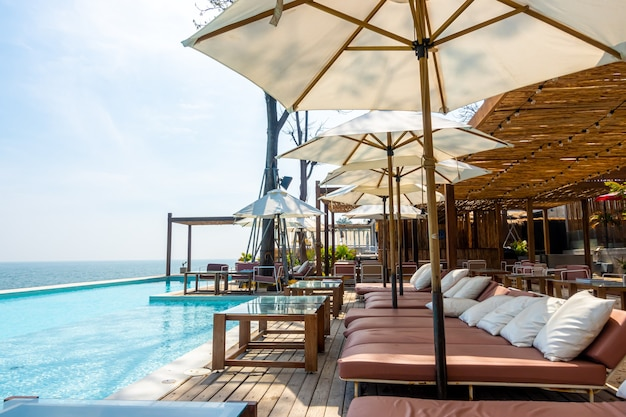 Beautiful and empty chair and umbrella with swimming pool and sea beach