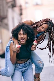 笑顔でアイスクリームを食べて美しい民族黒のガールフレンド