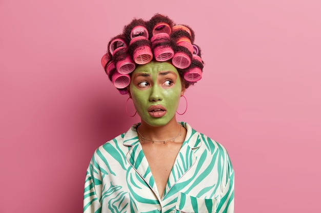 美しいエスニック女性は表情を心配し、目をそらし、細い線を減らすために緑の美容マスクを適用し、ピンクの上に隔離されたガウンを着ています。美容、ウェルネス、ヘアスタイリング