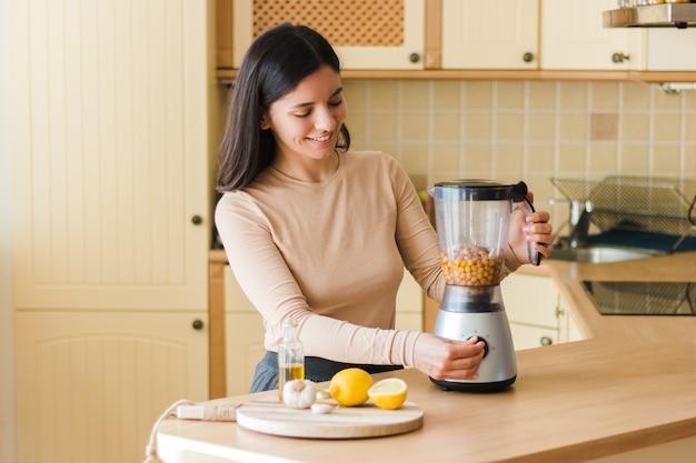 自然な菜食主義の食糧自家製ひよこ豆のフムスのレシピを準備する台所で魅力的な笑顔で美しい民族の女性