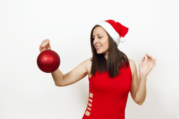 The beautiful european brunette young happy woman with charming smile in red dress and christmas hat holding big shiny tree toy on white background. santa girl isolated. new year holiday 2018 concept