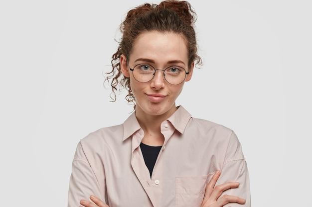 美しいヨーロッパの女性は、友人からの面白くない話を聞くのに退屈していると感じ、手を組んで、注意深く聞いているふりをし、黒い巻き毛をとかし、丸い眼鏡とシャツを着ています