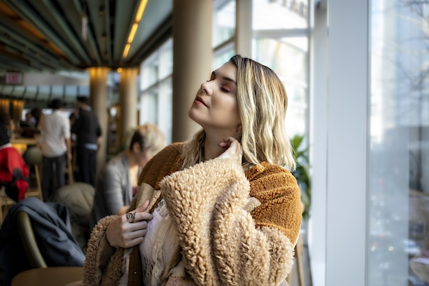 Beautiful european female wearing a fashionable orange coat and enjoying her time in a cafe