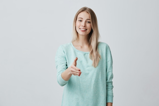 Beautiful european friendly woman with blonde long hair wearing casual blue sweater smiling broadly demonstrating her white perfect teeth and stretching her arm during introduction. body language