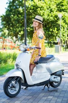 朝の公園でレトロなスクーターで黄色のドレスを着た美しいヨーロッパの女の子