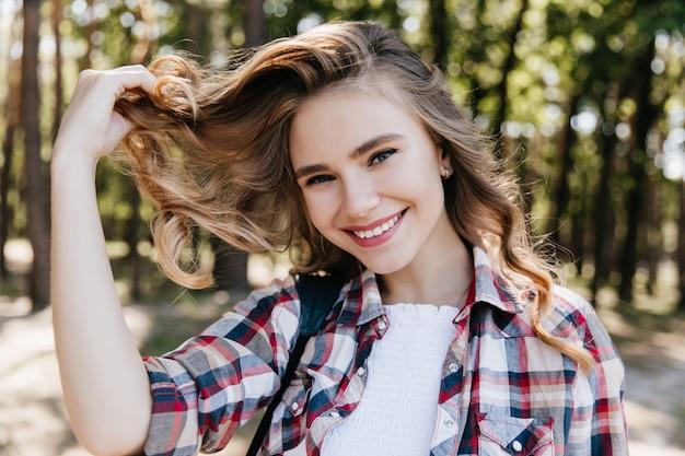 Bella ragazza europea che gioca con i capelli ricci nella foresta. outdoor ritratto di donna bianca adorabile che trascorre la mattina del fine settimana nel parco.