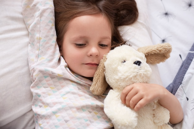 Красивая европейская девушка с темными волосами в светлой пижаме лежит в постели со своей мягкой белой игрушкой для собаки