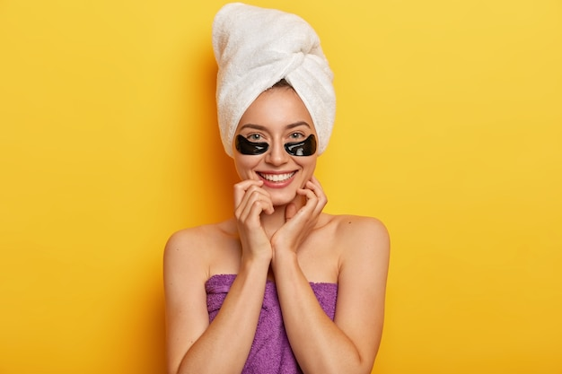 La bella signora europea ha una carnagione giovanile senza rughe, una pelle delicata, applica collagene scuro sotto le macchie degli occhi, ha un trattamento di ringiovanimento, fa la doccia, avvolto in un asciugamano pulito