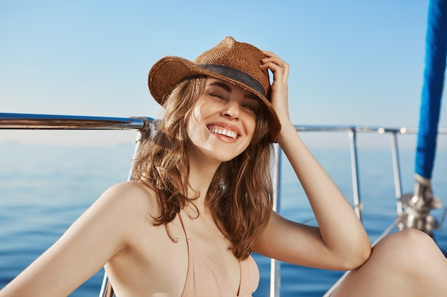 Beautiful european woman in bikini holding straw hat with hand while smiling broadly, sitting on floor of boat. young active cute woman enjoys warmth and seaside, ready to swim