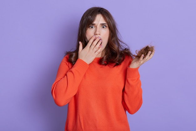 Beautiful european woman holding loosing hair, looks scared and amazed, covering opened mouth for surprise, disbelief face, looking with big eyes, has problem with hair, hair loos.
