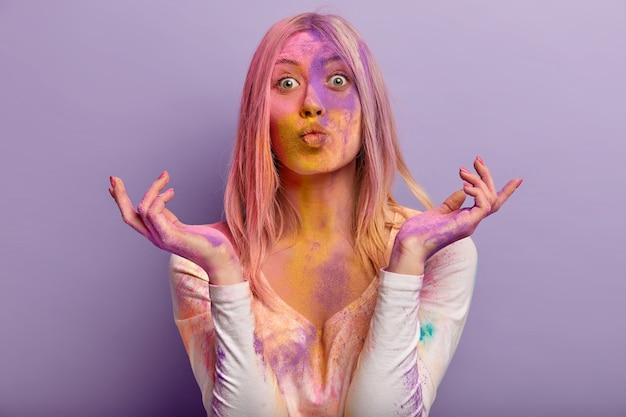 Красивая европейская женщина держит губы сложенными, удивленное выражение лица, разводит руки, носит повседневную одежду, намазанную цветным джемпером, изолированную на фиолетовой стене. концепция фестиваля холи