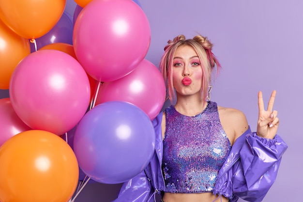 Beautiful european woman keeps lips folded makes peace gesture celebrates specical occasion poses with multicolored helium balloons