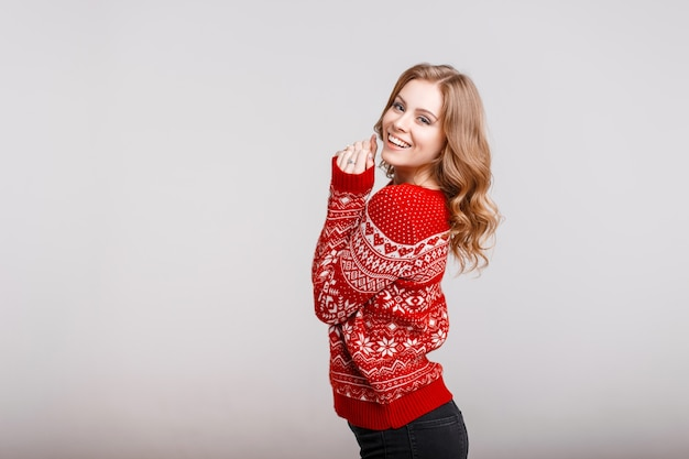 Beautiful european woman model in a trendy red sweater with a print in the studio