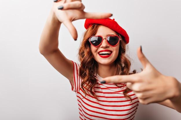 Bella donna europea in berretto rosso che esprime felicità. ragazza riccia emozionante in occhiali da sole che ride.