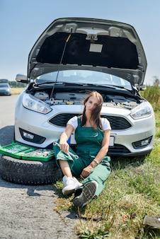 Beautiful european woman repairs the car on the road