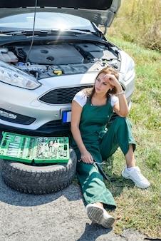 美しいヨーロッパの女性が道路で車を修理します