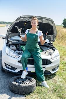 아름다운 유럽 여자는 도로에 차를 수리