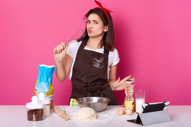 Beautiful european woman spends time at kitchen with whisk in one hand, wearing white t shirt, brown apron and red bright headband. attractive black haired lady isolated over pink wall.
