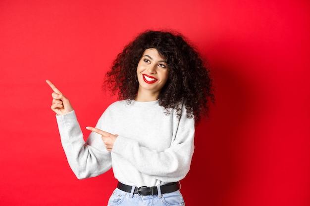 곱슬머리와 화장을 한 아름다운 유럽 여성, 손가락을 왼쪽으로 가리키고 꿈꾸는 듯한 미소로 옆을 바라보며 프로모션 거래, 빨간색 배경을 확인합니다.