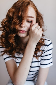 Beautiful european woman with wavy ginger hair posing with eyes closed. portrait of cute caucasian girl touching her face with hand.